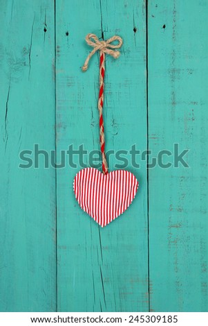 Red heart hanging by rope on antique teal blue shabby wooden background - stock photo