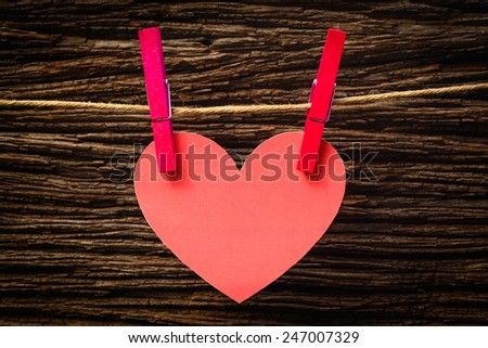 red heart hanging on the clothesline. On old wood background. - stock photo