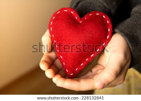 Red heart in child hands, gift, hand made valentine, close up, horizontal - stock photo