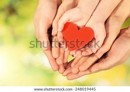 Red heart in family hands on bright background - stock photo