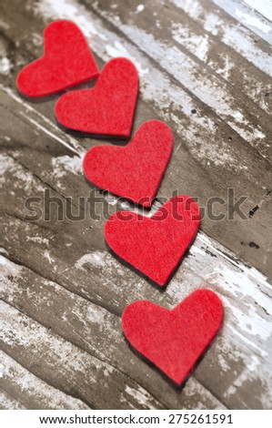red heart in felt on old whitened wooden background - stock photo