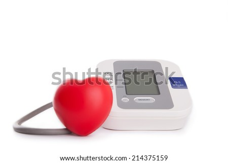 red heart in front of blood pressure meter isolated on white - stock photo