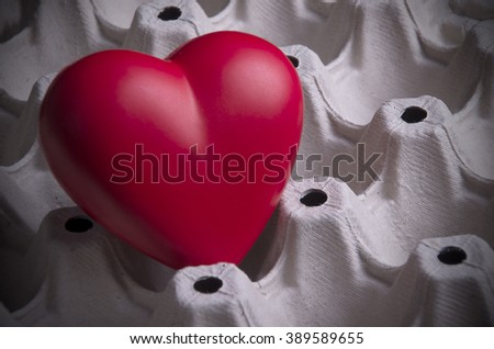 Red heart in paper carton for eggs.Fragility concept . (selective focus)