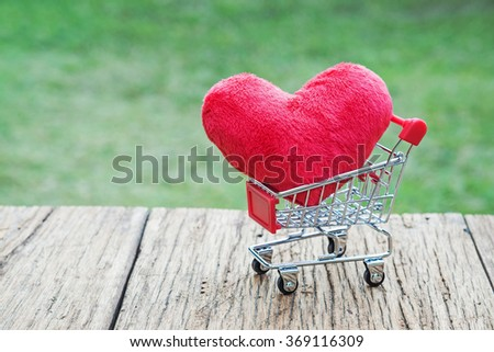 Red heart in shopping cart on wooden background.Valentine's Day concept. - stock photo