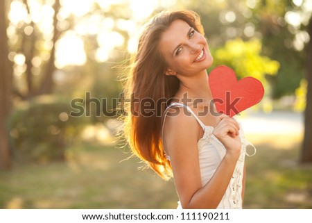 Red heart in the right hand of a young woman. Close-up - stock photo