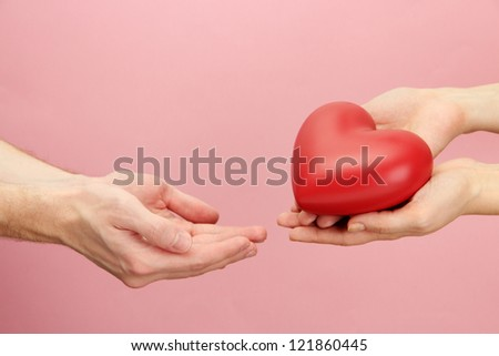 Red heart in woman and man hands, on pink background - stock photo
