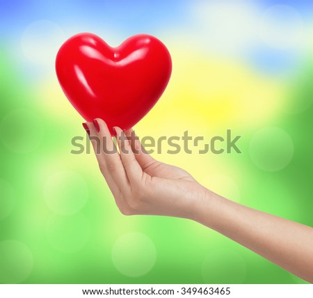 Red heart in woman hand over bright blurred nature background