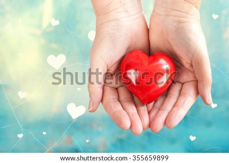 Red heart in woman Hands over vintage heart background - stock photo