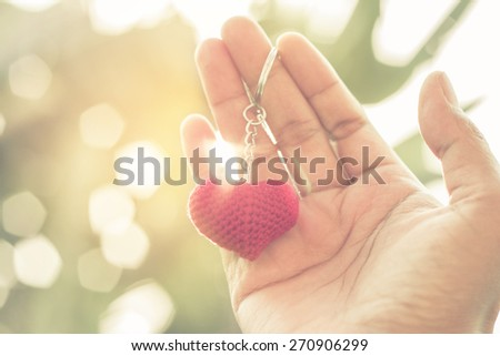 Red heart in woman hands with sunset light background.r - stock photo