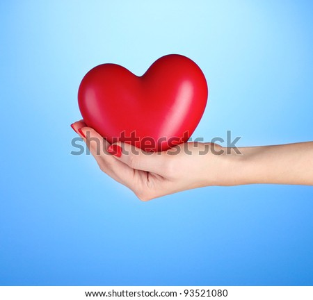 Red heart in woman's hand on blue background