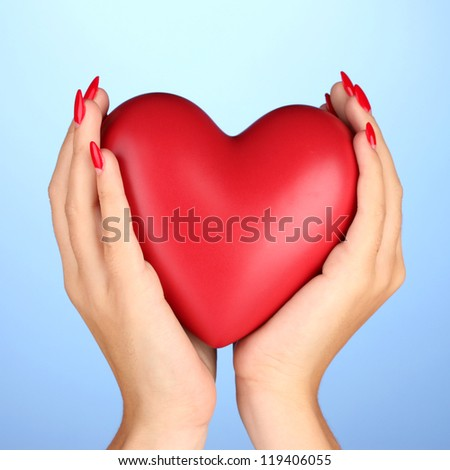 Red heart in woman's hands on color background