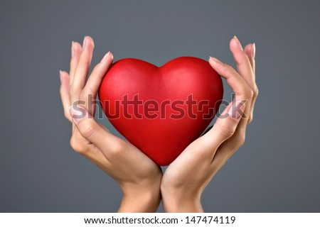 red heart in woman's hands on gray background