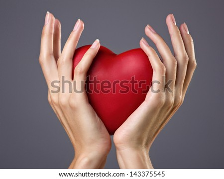 red heart in woman's hands on grey background