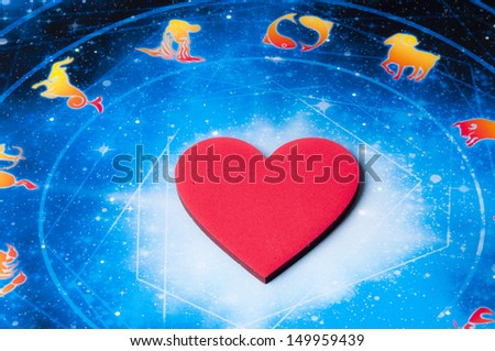 red heart lying on astrology background - stock photo