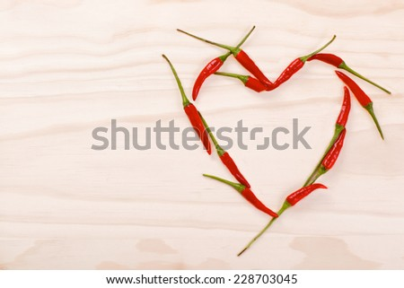Red heart made of red hot chilli peppers on a wooden background - stock photo