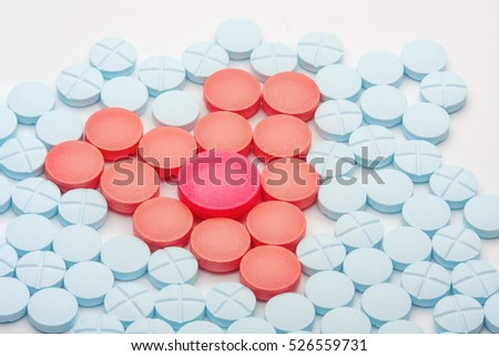 Red heart of medical tablets among blue pills