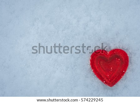 Red heart on a background of snow. Happy Valentine's day.