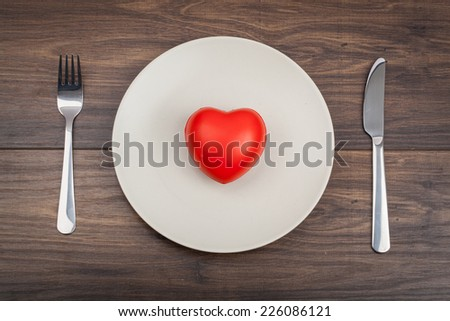 red heart on a plate, fork and knife on a wood background
