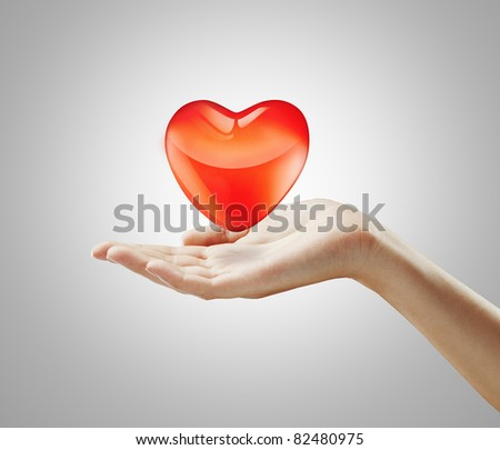 Red  heart on a woman's hand.Heart on the palm - love symbol - stock photo