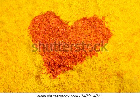Red heart on a yellow background from spices - stock photo