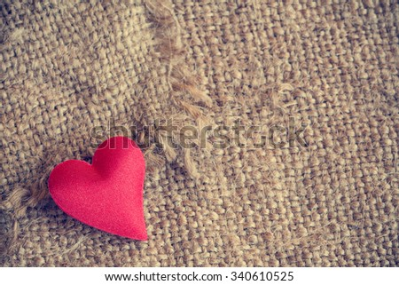 Red heart on gunny sackcloth texture background - stock photo