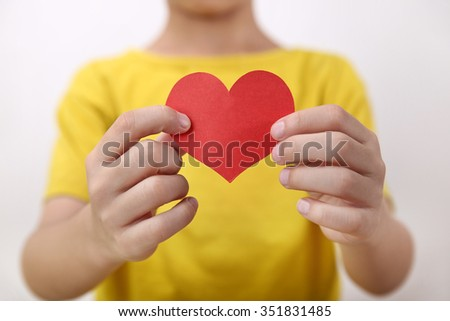 red heart on hand little boy   - stock photo