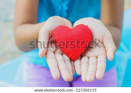 red heart on hand little girl - stock photo