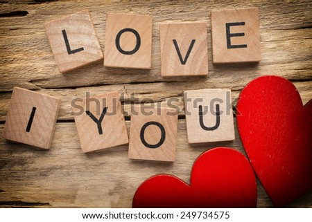 Red heart on old wooden background - Stock Image. I love you, cast out of wood kubik.