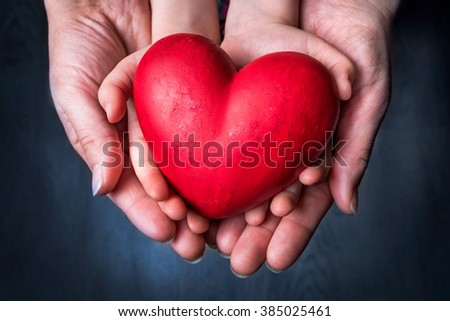 Red Heart on Palm of Woman and Child - Mother Day Symbol - stock photo