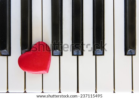 Red heart on piano - stock photo