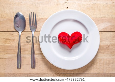 Red heart on plate on wooden background