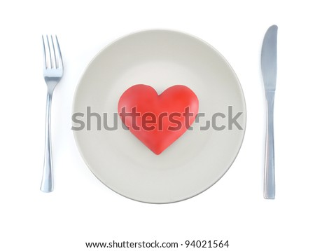 Red heart-on plate with fork and knife shot from above on white background