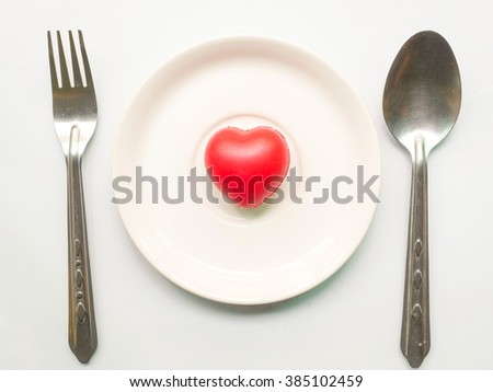 Red heart on plate with fork and spoon on white background.