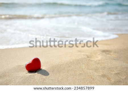 red heart on sandy sea beach - love relax concept - stock photo