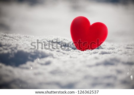 Red heart on snow, close up photo
