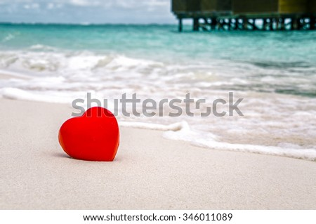 Red heart on the bank against the backdrop of water bungalows - stock photo