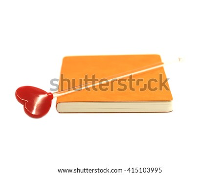 Red heart on the orange book isolated on white background, select focus.  - stock photo