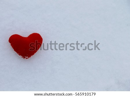 Red heart on the white snow