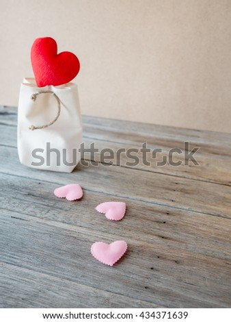 Red heart on white bag, pink hearts pattern on wooden table,