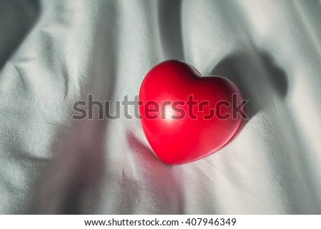 Red heart on white bed - stock photo