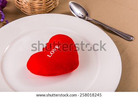 Red heart on white plate. - stock photo