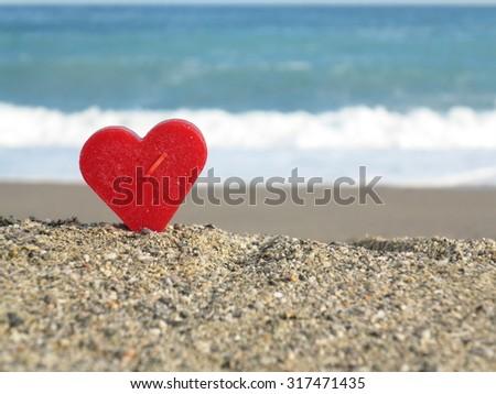 Red heart on white sand beach - stock photo