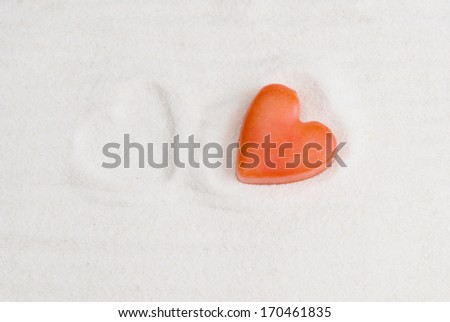 Red heart on white sand with a print of another heart next to it - stock photo