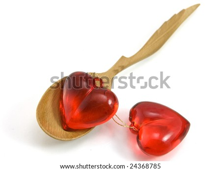 Red heart on wooden spoon isolated on a white background.