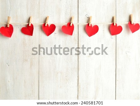 Red heart paper cut with clothes pin on white wooden background.Image of Valentines day - stock photo