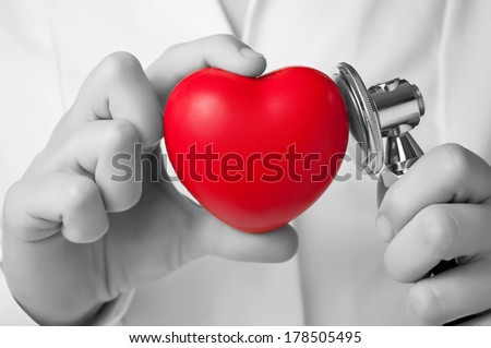 Red heart shape and stethoscope in a doctor's hand - stock photo