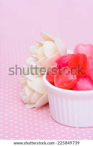 Red heart shape candy on pink tablecloth