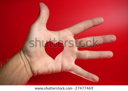 Red heart shape draw on a male human hand, red background [Photo Illustration] - stock photo