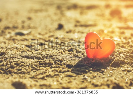 red heart shape on sunset beach under warm light. abstract background love summer on the beach. - stock photo