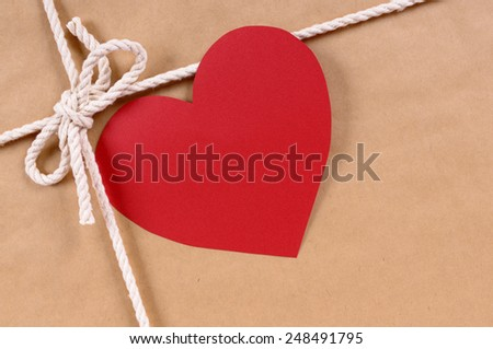 Red heart shape valentine card or gift tag on a brown paper package or gift background tied with string.  Space for copy. - stock photo